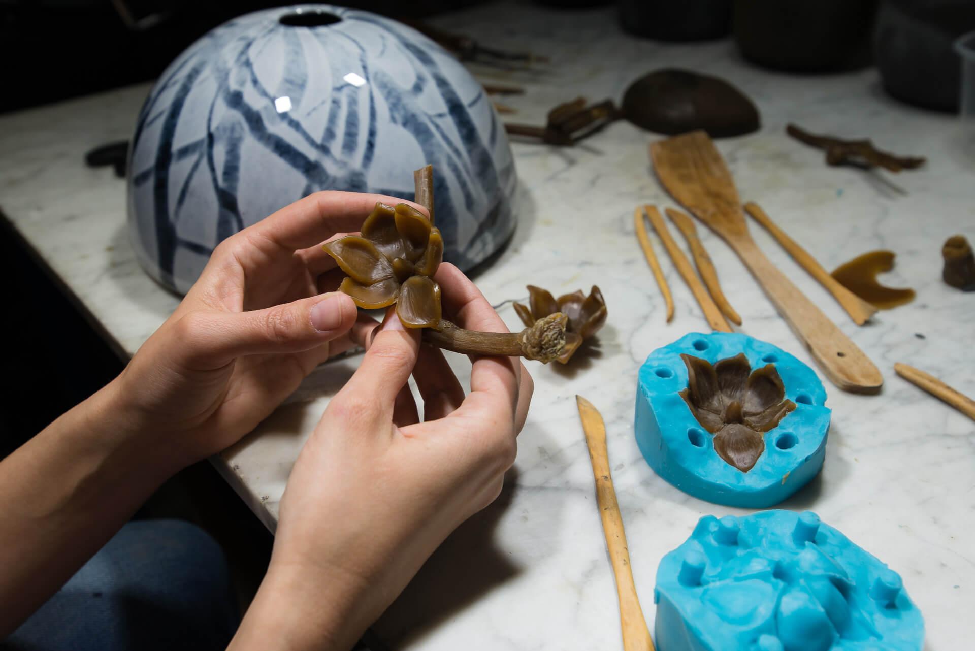 Fabrication d'un élément en cire pour completer un bouchon d'urne funéraire en verre soufflé fabriqué à l'atelier de verre Welmo