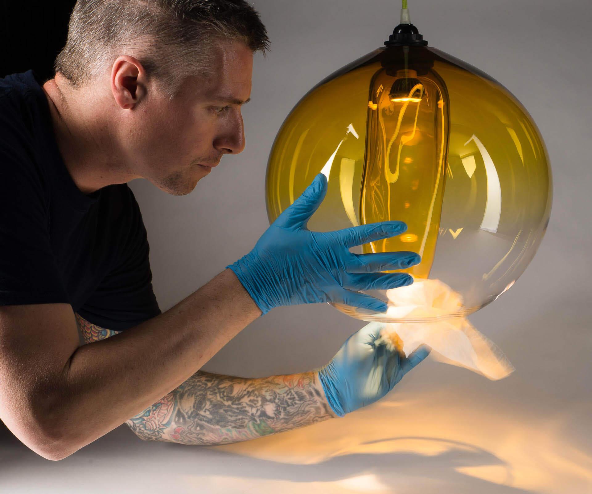 Patrick Primeau, souffleur de verre, nettoie un luminaire en verre soufflé fabriqué à l'atelier de verre Welmo