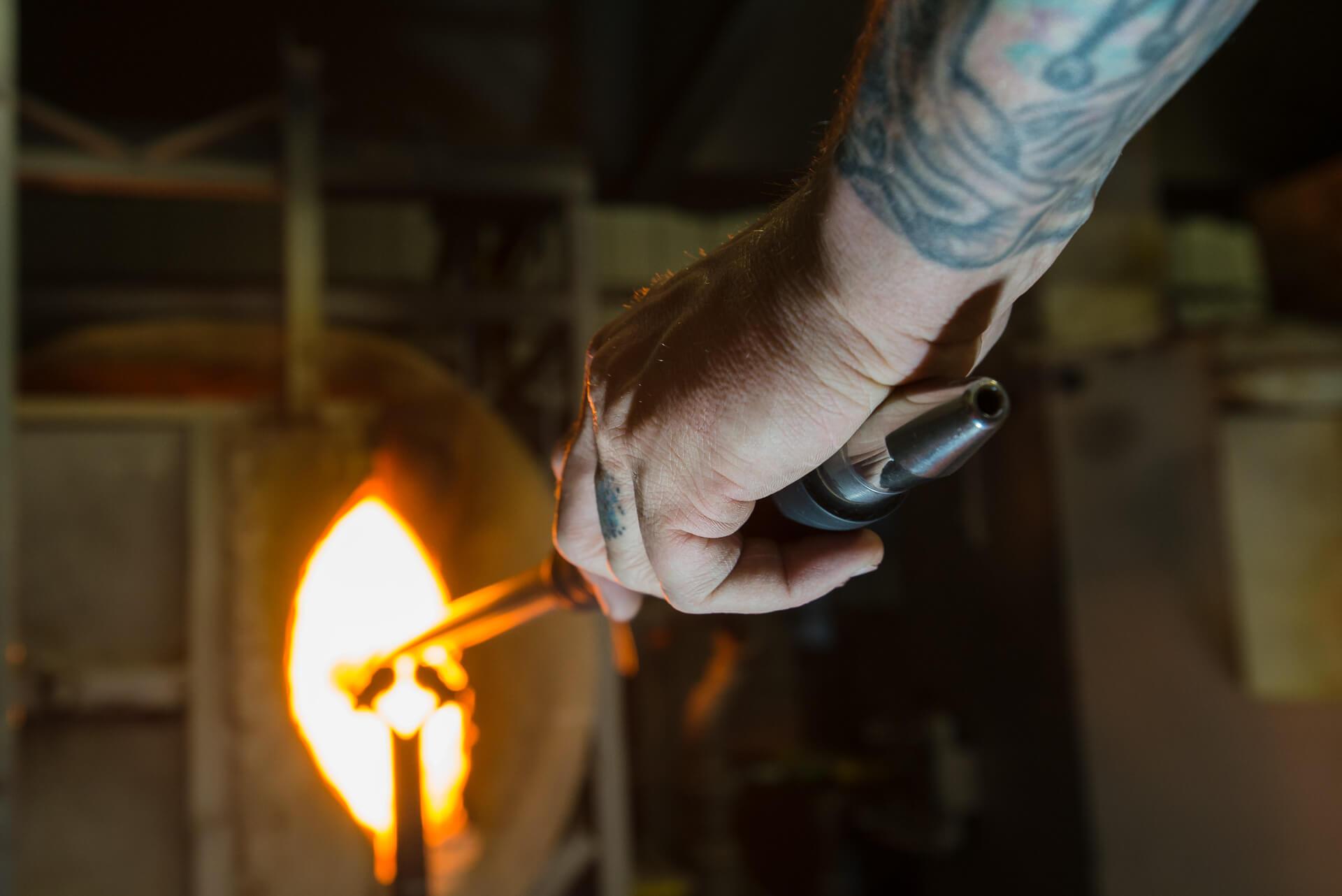 main du souffleur de verre Patrick Primeau tenant la canne à souffler au four à l'atelier de verre Welmo
